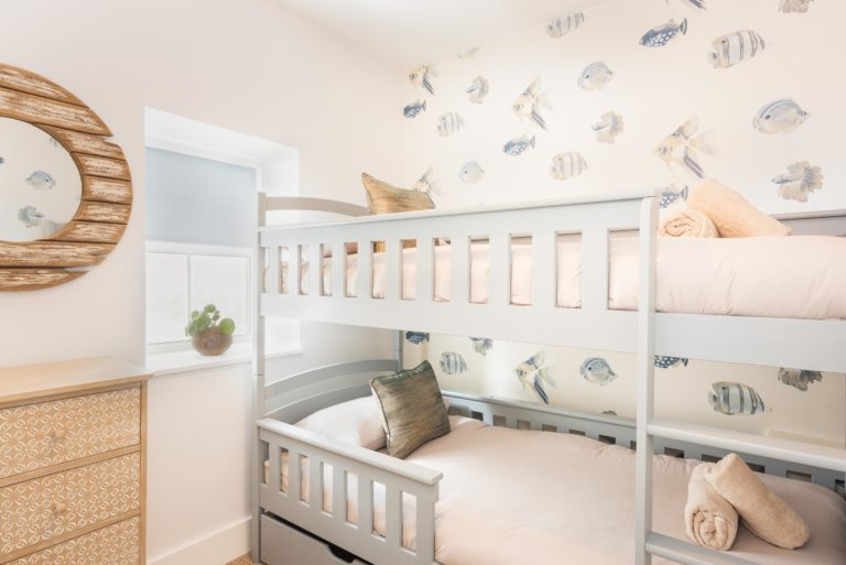 bunk beds in holiday cottage with fish theme wallpaper