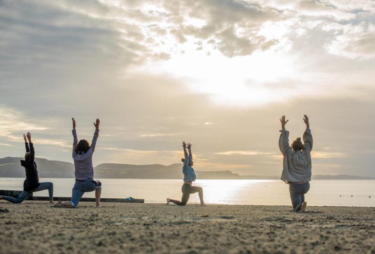 Lyme Regis group yoga class with morning sunrise